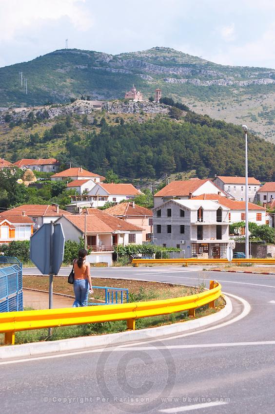 Street scene in Trebinje, a main road and a woman walking, the monastery Gracanica on the historic hill known as Crkvina in the background. Trebinje. Republika Srpska. Bosnia Herzegovina, Europe.