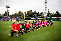 TACOMA, WA - JULY 31: OL Reign kneel together during the national anthem before a game between Racing Louisville FC and OL Reign at Cheney Stadium on July 31, 2021 in Tacoma, Washington.