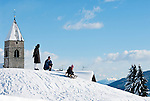 Italy, Alto Adige (South Tyrol), Maranza: father, mother and son sledging