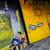 A Salvadoran man reads newspapers in front of a car mechanic workshop's gate, decorated by a hexagram, on the street in San Salvador, El Salvador, 7 April 2018.