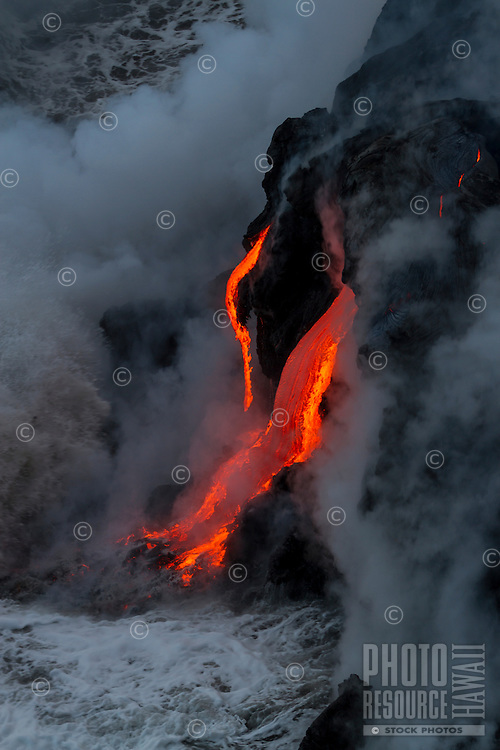 Lava flows and drips into the ocean as the sea cools the new creation of land near Hawai'i Volcanoes National Park and the Kalapana border, Big Island.