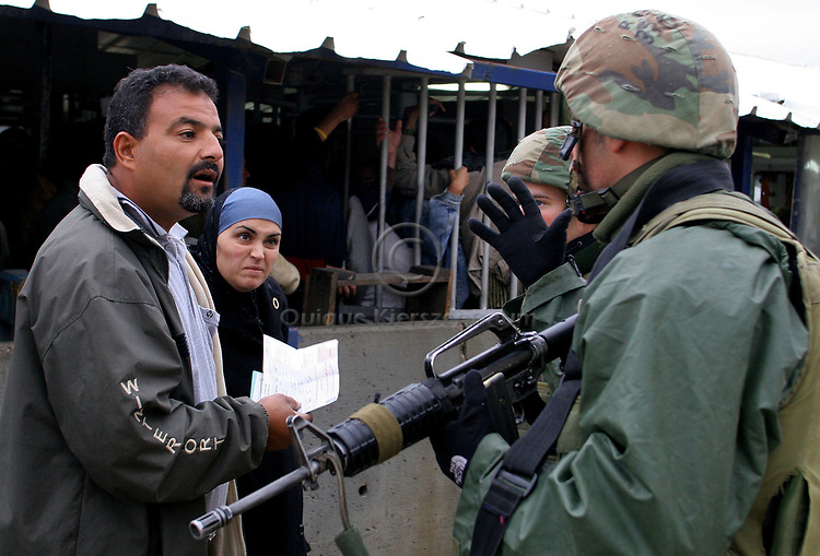 A Palestinian couple argues with Israeli soldiers as they prevent them from crossing the Hawara checkpoint in Nablus, West Bank, November 05, 2006. The Hawara checkpoint on the southern entrance of Nablus controls the movement of Palestinians between Nablus and the Southern part of the West Bank. The checkpoint, run by IDF paratroopers, doesn't limit with Israel. Photo by Quique Kierszenbaum