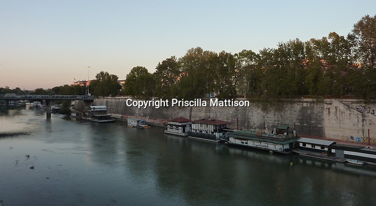 Rome, Italy - October 6, 2012:  Houseboats line the Tiber at sundown.