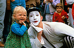 Mime performing at street fair mimicing a little girls expressions and hand gesture
