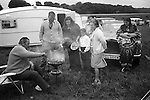 A wealthy gypsy family barbecue, with Rolls Royce and caravan, Derby Day horse race,  Epsom Downs, Surrey, England 1974.<br /> <br /> George James Butcher, sitting at the BBQ.<br /> Lorraine Nethercott leaning against her fathers car.