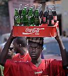 A man carries soft drinks on his head as he walks along a street in Port-au-Prince, Haiti.