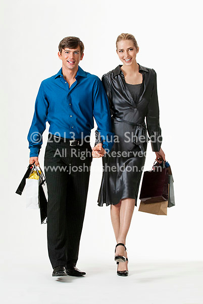 Young couple walking, carrying shopping bags
