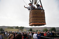 Riders wave to the crowd as a balloon takes off from the ground at the Great Prosser Balloon Rally in Prosser, Washington, USA.