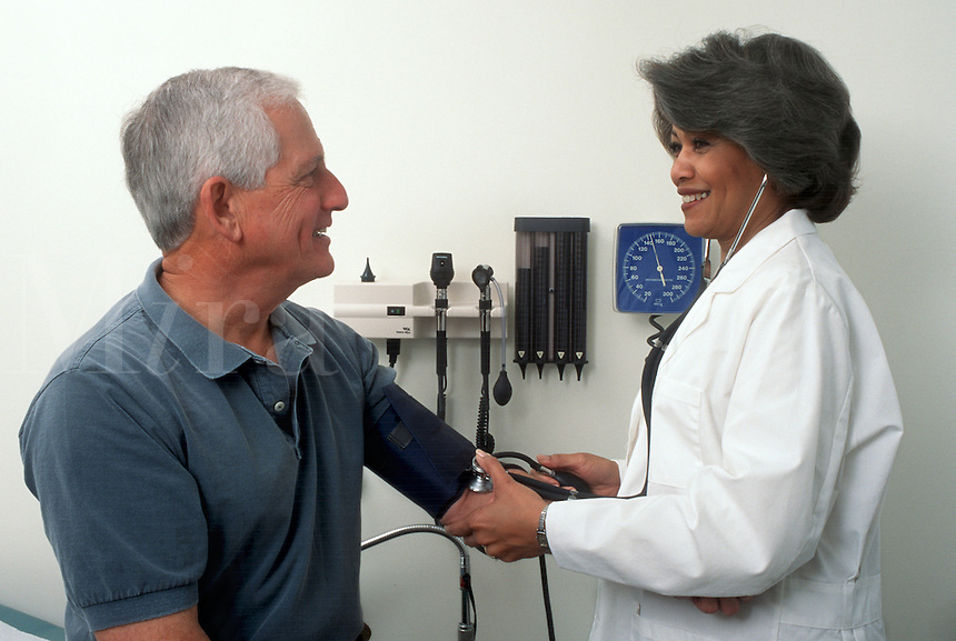 A doctor takes a patient's blood pressure during an office visit. Vital signs.