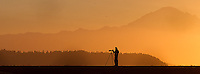 A photographer waits for birds to fly by as the sun rises over Boundary Bay.