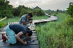 Fishing Cat (Prionailurus viverrinus) biologists, Anya Ratnayaka and Tharindu Bandara, smelling fishing cat urine in urban wetland, Urban Fishing Cat Project, Diyasaru Park, Colombo, Sri Lanka