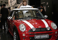 A visitor poses inside of a Mini Cooper at the Auto Shanghai 2005 in Shanghai, China. Red Flag was renowned in China as the car for heads of state and high officials before western automakers edged in with their own luxury makes..