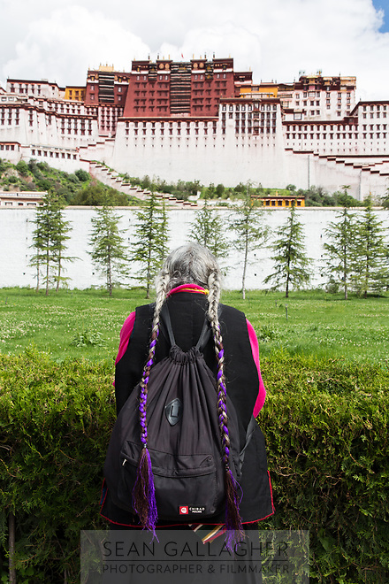 A woman prays in front of the Potala Palace in Lhasa. One of the spiritual centers of Tibet, thousands of pilgrims visit each day, journeying here at least once in their lifetimes. They walk clockwise around the palace, pausing to pray and take in the sacred structure before them.