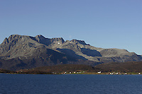 Moon rising over mountain landscape behind small norwegian village at the edge of fjord. Tromso, Arctic Norway