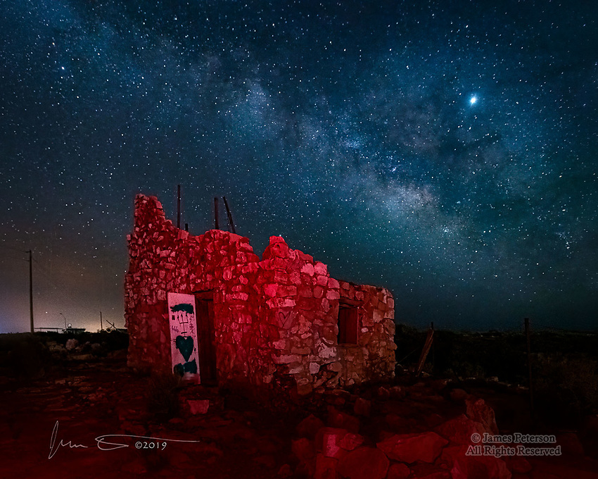 Milky Way over Two Guns, Arizona ©2019 James D Peterson.  Two Guns was a tourist stop between Winslow and Flagstaff during the heyday of Route 66.  It had a tiny zoo, a gas station, curio shops, and a small residential community, all constructed of stones that were plentiful in the area.  Most of it has fallen down in the days since Route 66 was bypassed, and what remains constitutes a spooky ghost town, especially when photographed at night.<br /> <br /> On this evening, the Milky Way (and the planet Jupiter, the bright object in the upper right) were visible above a low-hanging plume of smoke from a forest fire in the region, and the city lights of Winslow are lighting up the smoky haze on the left.  To create the eerie red glow, I light painted the structure with a small LED headlamp during a 15 second exposure.