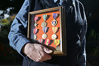 Albert King holds his medals, Friday, October 2, 2020 at the Fayetteville Square in Fayetteville. Check out nwaonline.com/2010010Daily/ for today's photo gallery. <br /> (NWA Democrat-Gazette/Charlie Kaijo)