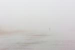 Couple walks in fog on Bonge Beach, near Westport, Washington.