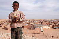 A boy smiles on December 12, 2003, in the Saharawi refugee camps. Saharawi people have been living at the refugee camps of the Algerian desert named Hamada, or desert of the deserts, for more than 30 years now. Saharawi people have suffered the consecuences of European colonialism and the war against occupation by Moroccan forces. Polisario and Moroccan Army are in conflict since 1975 when Hassan II, Moroccan King in 1975, sent more than 250.000 civilians and soldiers to colonize the Western Sahara when Spain left the country. Since 1991 they are in a peace process without any outcome so far. (Ander Gillenea / Bostok Photo)