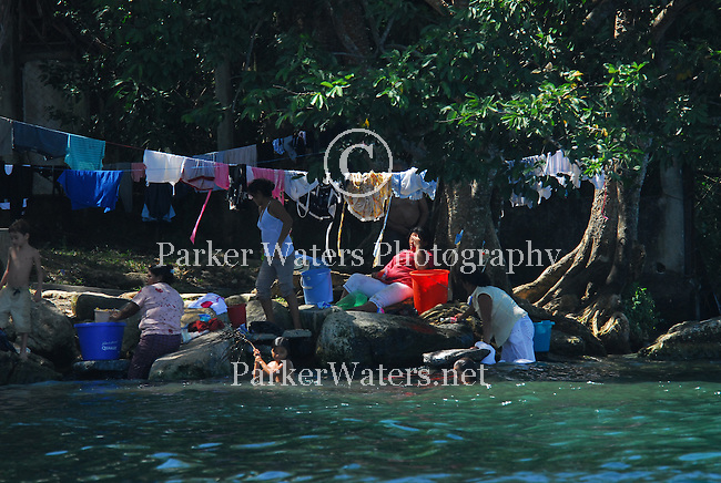 Locals do their laundry along the banks of the Rio Dulce in Guatemala.