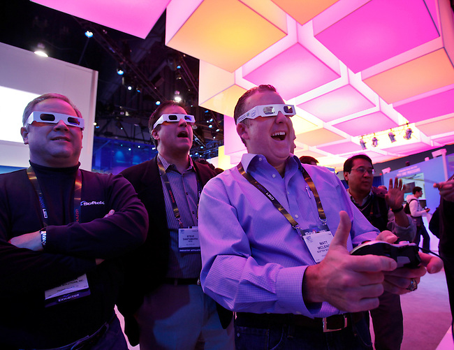 Attendee Matt McLennon, right, uses 3-D glasses as he plays a 3-D game on and Intel-powered computer at the Intel exhibit at the Consumer Electronics Show (CES) in Las Vegas, Thursday, Jan. 7, 2010. (AP Photo/Paul Sakuma)