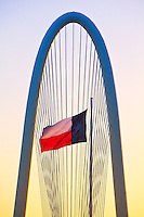 """""""Margaret Hunt Hill Bridge at Sunrise"""" – Standing in front of The Margaret Hunt Hill Bridge, the Lone Star Flag flutters in the wind as the morning sun breaks the horizon. Positioned across the Trinity River, The Margaret Hunt Hill Bridge – positioned West of downtown Dallas – was designed by Spanish architect Santiago Calatrava and opened in March 2012."""