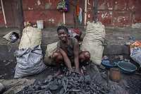Haiti, Gros-Morne. Women vendors selling charcoal in the market. They make about $5-$7 a day.