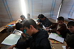 """Eighth-grade boys attend religion class at the school in Azaz Camp, just inside the Syrian border with Turkey, Feb. 26, 2013. A private charity donated the tents for the school, which has around 800 students between the ages of 6 and 16. Desks and other materials were salvaged from schools in Azaz village a few kilometers away. The school opened two months ago, and because there are so many children, they attend either a morning or an afternoon session, learning math, Arabic, English, and religion. Almost all of the teachers and staff are refugees and reside in the camp. The children come to school with special challenges--they may have psychological distress because of traumatic events or health problems due to poor living conditions in the camp, and some have not been in school for a long time and have to catch up to their grade level. """"We try everything to make them happy,"""" said a teacher, Abdul Razaq. According to administrators, this camp holds roughly 9,000 to 10,000 internally displaced persons (IDP's). Two meals per day are provided by a Turkish humanitarian organization, and Qatar Red Crescent provided tents. There is very little electricity, and no running water. There is also a refugee camp on the Turkish side of the border, but it is full. The UN Refugee Agency has reported a sharp increase in refugees fleeing Syria for neighboring countries in the first months of 2013."""