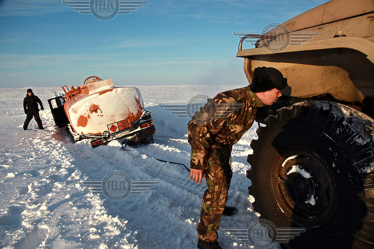 A man tries to release a truck carrying diesel that is stuck in deep snow in  Naryan-Mar in Russia's Arctic far north. /Felix Features