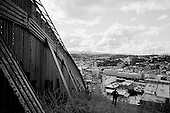 Nogales, Arizona.USA.October 25, 2006..The US border patrol watches along the border fence that separates Nogales, Mexico and Nogales USA. The fence extends for several miles in either direction off the port of entry - then there is little to stop people from crossing illegally. Nogales is flooded with Mexicans legal and illegal and is mostly a transit and shopping town.