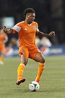 Houston Dynamo midfielder Giles Barnes (23) dribbles. In a Major League Soccer (MLS) match, Houston Dynamo (orange) defeated the New England Revolution (blue), 2-1, at Gillette Stadium on July 13, 2013.