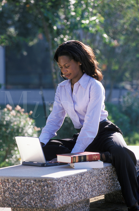 college student using laptop computer seated on bench