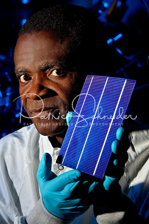 Professor Aba Ebong, holding a solar cell that will be created in the solar cell research labs on the UNC  Charlotte Campus..PEISL, the Power, Energy and Intelligent Systems Lab at the University of North Carolina Charlotte (UNC Charlotte / UNCC) within the department of Electrical and Computer Engineering. PEIS Research Laboratory helps students study intelligent system applications to electrical power and energy systems related to intelligent power systems controls.
