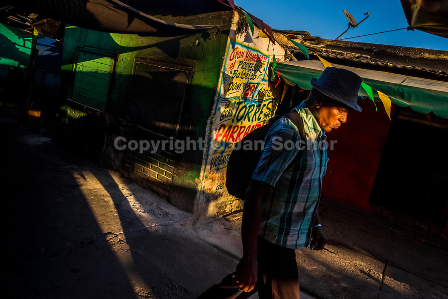 An Afro-Colombian market vendor walks around the wall, covered with Champeta music propaganda, in the market of Bazurto in Cartagena, Colombia, 6 December 2018. Far from the touristy places in the walled city, a colorful, vibrant labyrinth of Cartagena's biggest open-air market sprawls to the Caribbean seashore. Here, in the dark and narrow alleys, full of scrappy stalls selling fruit, vegetables and herbs, meat and raw fish, with smelly garbage on the floor and loud reggaeton music in the air, the African roots of Colombia are manifested.