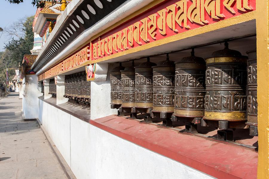 Nepal, Kathmandu, Swayambhunath.   Buddhist Prayer Wheels Line the Wall around the Stupa at the Base of the Hill.