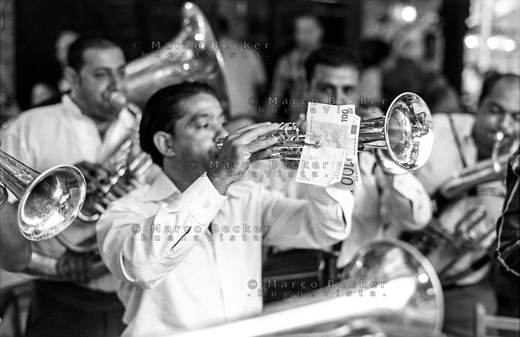 Festival di trombe e ottoni di Guca (Cacak). Una banda suona all'interno di un ristorante, Il trombettista tiene sulla tromba diverse banconote da 100 euro che degli avventori del locale gli hanno dato per avere appresso la banda --- Trumpet festival of Guca (Cacak). A band playing inside a restaurant. The trumpeter has on his trumpet several 100 euros banknotes that customers gave him in order to have the band playing for them nearby