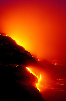 Vivid fiery streams of lava flow from cliffs into the ocean.