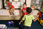 Preschool ages 3-5 two boys playing mock fighting game horizontal