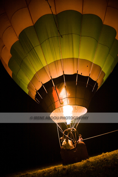 """Hot air balloonists  at the 2008 Shenandoah Valley Hot Air Balloon Festival at Historic Long Branch in Millwood, Virginia fire a propane burner to heat the air in the balloon """"envelope,""""  causing the balloon to stand up and fly."""
