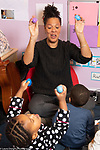 Education preschool toddler-2s music enrichment female teacher leading group in song with children shaking eggs