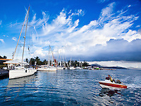 Tahitian family approaches Uturoa Harbor in small power boat, with yachts tied to dock, and dramatic clouds above