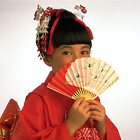 Portrait of a young Japanese girl in a traditional kimono, peering out shyly from behind a fan.