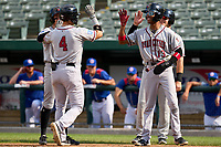 Quad Cities River Bandits Michael Massey (4) high fives teammates Nick Loftin (2), Maikel Garcia (13) and Gavin Stupienski (43) after hitting a home run during a game against the South Bend Cubs on August 20, 2021 at Four Winds Field in South Bend, Indiana.  (Mike Janes/Four Seam Images)