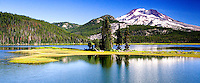 Fine art panorama travel landscape of Sparks Lake, with green island strip supporting a few tall pine trees in the middle of the lake, and an edge of pine trees, hills, and Mount Bachelor in the background, Central Oregon, U.S.A.