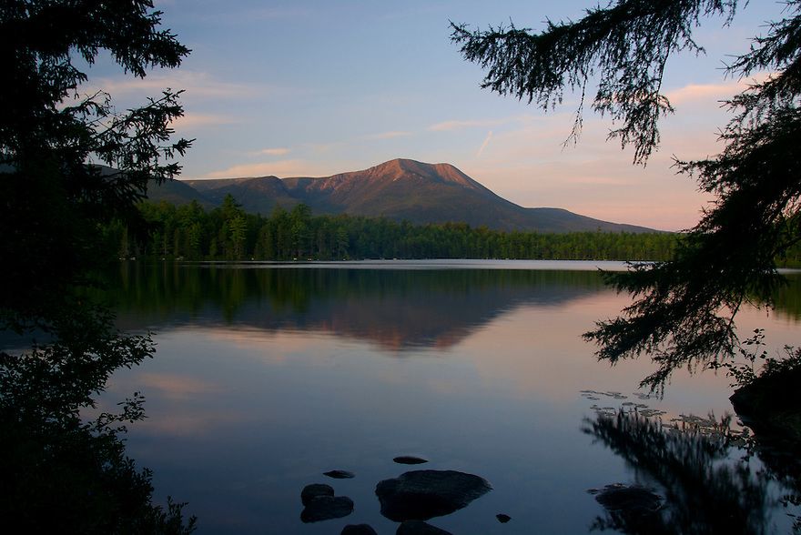 Calm spreads across the landscape of Baxter State Park as the last rays of sunlight strike western flanks of Mt Katahdin.