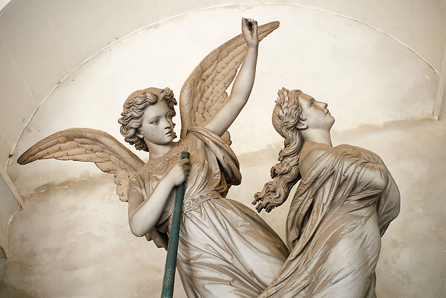 Picture and image of an angel guiding a women to heaven stone sculpture on the Piaggio tomb sulpted by Fabian Federico 1876. Section A, no 45, The  monumental tombs of the Staglieno Monumental Cemetery, Genoa, Italy