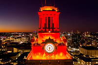 This is a close up aerial view of the UT Tower in downtown Austin, a landmark with the top of the tower orange. The UT tower can be seen from many places in downtown Austin because it is 307 feet tall and is located in the center of campus at the University of Texas. The tower is part of the Austin cityscape. The tower top is orange for a sports victory such as a football game or a special event.