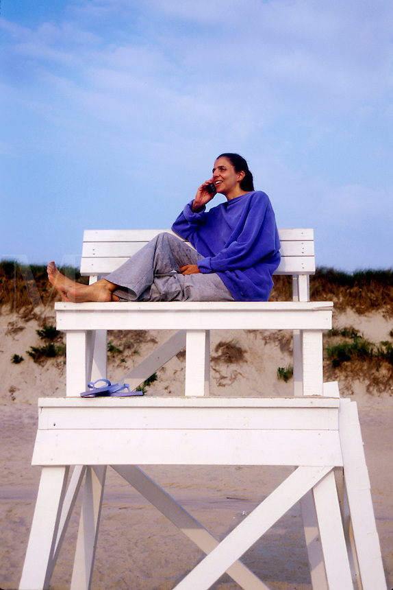 Woman sits on the beach talking on a cell phone.