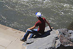 Young man sits along river in Denver, Colorado. .  John offers private photo tours in Denver, Boulder and throughout Colorado. Year-round Colorado photo tours.