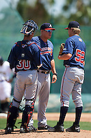 GCL Braves pitching coach Christopher Roque (24) talks with catcher Collin Yelich (30) and relief pitcher Ryan Schlosser (52) during a game against the GCL Pirates on August 10, 2016 at Pirate City in Bradenton, Florida.  GCL Braves defeated the GCL Pirates 5-1.  (Mike Janes/Four Seam Images)