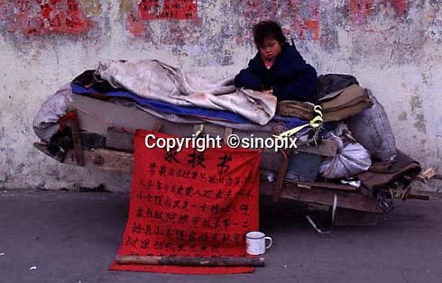 A baby girl sits on a wagon in Guangzhou, china, the sign advises that the child, a girl, is for sale.   China's one child policy has resulted in a nation of spoilt children, where boys outnumber gils by almost 20 in every hundred, and girls are often dumped or sold. <br /> ©sinopix